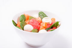Salad with smoked salmon, grapefruit, spinach and mozzarella wit. H olive oil dressing in white bowl on a white background Stock Photo