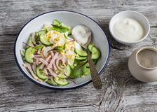 Salad with smoked turkey, cucumber and boiled egg on a light rustic wooden background. Royalty Free Stock Photography