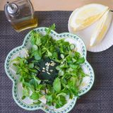Salad with spirulina. Healthy food concept. Fresh cornsalad with spirulina powder in the bowl, a bottle of olive oil and two pieces of lemon on the table stock photography