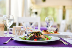 A salad in spring restaurant with violet napkins. Fresh salad in cafe colourfull meal. Vertical photo. With mushrooms Royalty Free Stock Photography
