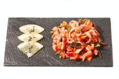 Salad with squid on a black plate with lemon Royalty Free Stock Photography