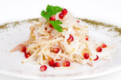 Salad with squid, onion, apple and pomegranate. On the plate Stock Photo