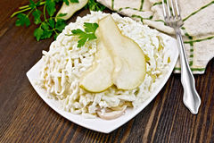 Salad of squid and pears with parsley on dark board Royalty Free Stock Photos