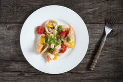 Salad with squid rings, shrimps, pepper and tomatoes Royalty Free Stock Photo