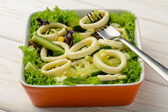 Salad with squid rings and vegetables on wooden table. Royalty Free Stock Photo