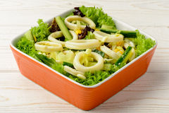 Salad with squid rings and vegetables on wooden table. Royalty Free Stock Image