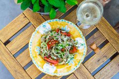Salad with squid, tomato and radish on a yellow plate top view. Horizontal Royalty Free Stock Images
