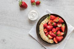 Salad of strawberries and banana on a dark plate on a light background. stock photography