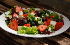 Salad, strawberries, cheese, tomatoes, olives stock photos