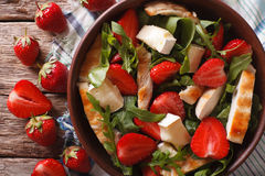 Salad with strawberries, chicken, cheese and arugula closeup. Salad with strawberries, grilled chicken, cheese and arugula close-up on the table. horizontal view royalty free stock photo