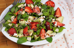 Salad with strawberries. Salad spinach with strawberries, avocado, mint, ricotta and sesame,poppy seeds Royalty Free Stock Photos
