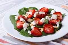Salad with strawberries, spinach and goat cheese on a plate Stock Images