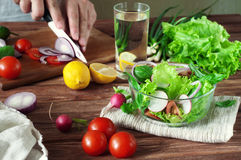 Salad of summer vegetables in a deep bowl of glass. Arugula, lettuce, radishes, onions, cherry tomatoes. In the background male hand sliced onions on cutting Royalty Free Stock Photography