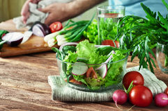 Salad of summer vegetables in a deep bowl of glass. Arugula, lettuce, radishes, onions, tomatoes. In the background a men preparing salad. Concept healthy Stock Photo