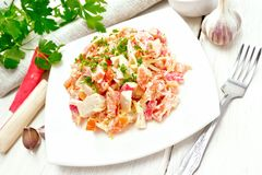 Salad of surimi and tomatoes with mayonnaise on wooden table stock photography