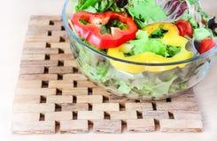 Salad and teak plate mat close-up Stock Photography