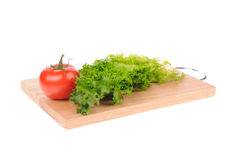 Salad and tomato on cutting board Stock Image