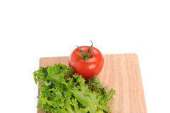 Salad and tomato on cutting board Stock Photography