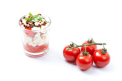 Salad with tomato and feta cheese in glass, white background Royalty Free Stock Photo
