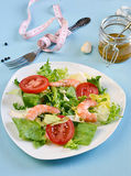 Salad with tomato, king shrimps and sauce vinaigrette. On blue background stock photo