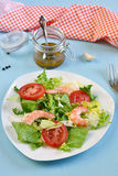 Salad with tomato, king shrimps and sauce vinaigrette. On blue background stock photography
