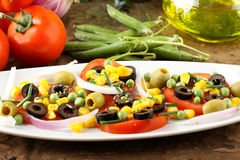 Salad of tomato, olives, corn and peas stock images