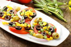 Salad of tomato, olives, corn and peas Stock Photos