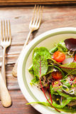 Salad with tomato and radish sprouts for dinner. On a wooden background Royalty Free Stock Photography