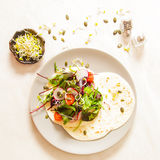 Salad with tomato and radish sprouts for dinner. On a wooden background Stock Photos