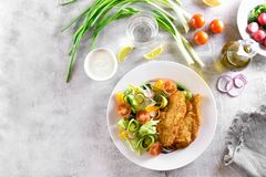 Salad from tomato, zucchini, radish, greens and schnitzel. On plate over stone background with copy space. Top view, flat lay Royalty Free Stock Photo