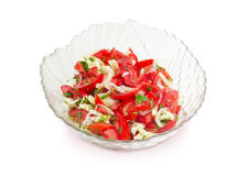 Salad of the tomatoes, bell pepper and onion. Vegetable salad of a fresh sliced tomatoes, white bell pepper, onion and potherb in a glass salad bowl on a white Royalty Free Stock Photo