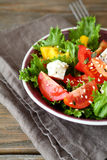 Salad with tomatoes, cheese and greens in a bowl on napkin Stock Photos
