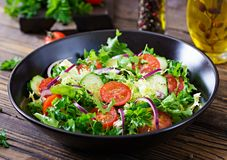 Salad from tomatoes, cucumber, red onions and lettuce leaves. Healthy summer vitamin menu. Vegan vegetable food. Vegetarian dinner table stock photography