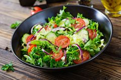 Salad from tomatoes, cucumber, red onions and lettuce leaves. Healthy summer vitamin menu. Vegan vegetable food. Vegetarian dinner table stock photo