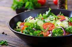 Salad from tomatoes, cucumber, red onions and lettuce leaves. Healthy summer vitamin menu. Vegan vegetable food. Vegetarian dinner table royalty free stock images