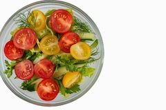 Salad of tomatoes, cucumbers, dill and parsley in a plate on a w. Hite background stock photography