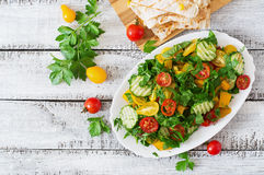 Salad of tomatoes, cucumbers, peppers, arugula and dill. Stock Photography