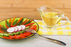 Salad from tomatoes, cucumbers, radishes and peppers in plate. And jug of vegetable oil on table Royalty Free Stock Image