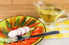 Salad from tomatoes, cucumbers, radishes and peppers in plate. And jug of vegetable oil on table Stock Images