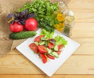 Salad with tomatoes, cucumbers and some ingredients for its prep. Vegetable salad with fresh sliced tomatoes and cucumbers and greens on square white dish and royalty free stock photo