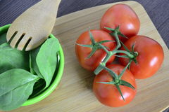 Tomato at its best. Tomatoes  on a cutting board next to some greens Royalty Free Stock Photography