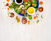 Salad with tomatoes, feta cheese, mustart balsamic vinaigrette and greens variation, in blue plate. On white wooden background, top view, frame stock photos