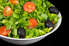 Salad with tomatoes, lettuce and olives. Isolated on black background Stock Photos