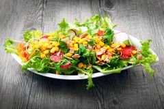 Salad with tomatoes and mais on wooden table Stock Image