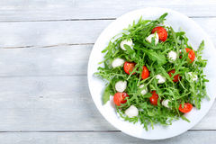 Salad with tomatoes, mini mozzarella, arugula, close-up. Dietary low calorie delicious salad with tomatoes, mini mozzarella, arugula on a white dish on a white stock image