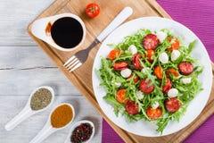 Salad with tomatoes, mini mozzarella, arugula, fried sausages. Delicious salad with tomatoes, mini mozzarella, arugula, fried sausages on a white dish Royalty Free Stock Images