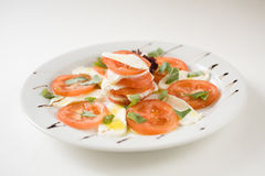 Salad with tomatoes and mozzarella cheese. On a white plate royalty free stock image