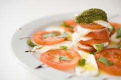 Salad with tomatoes and mozzarella cheese. On a white plate, detail royalty free stock photo