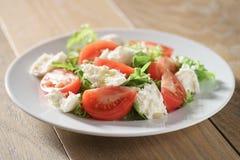 Salad with tomatoes, mozzarella, rocket salad and cedar nuts Stock Photo