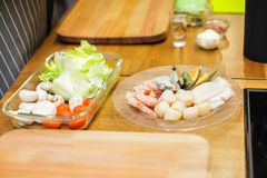 Salad, tomatoes,mushrooms and raw Fresh seafood lies on glass plate in front of the stove while waiting for cooking.  Royalty Free Stock Image